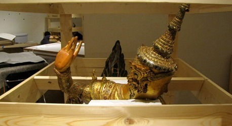 A male kinnara statue (Konbaung Period, 1752–1885) appears as though he is waving goodbye  before his custom crate is boxed up for shipment to the Asia Society in New York. (Photo credit: Pete Olson)