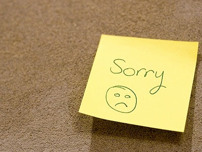 "Photo of ""Sorry"" and a sad face on a sticky note"
