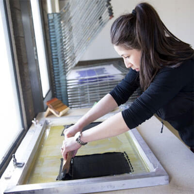 An NIU printmaking student creates her work of art.
