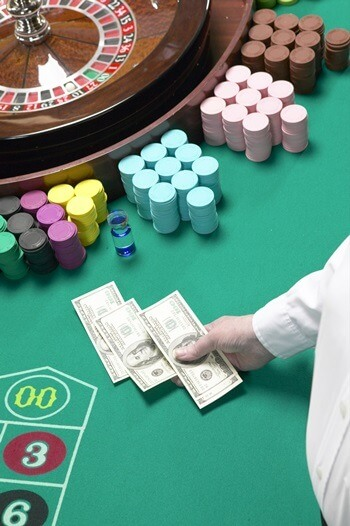 Man holding banknotes at roulette table