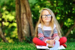 Adorable little girl with a book in the park