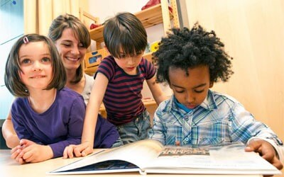 Photo of kindergarten children reading with a teacher
