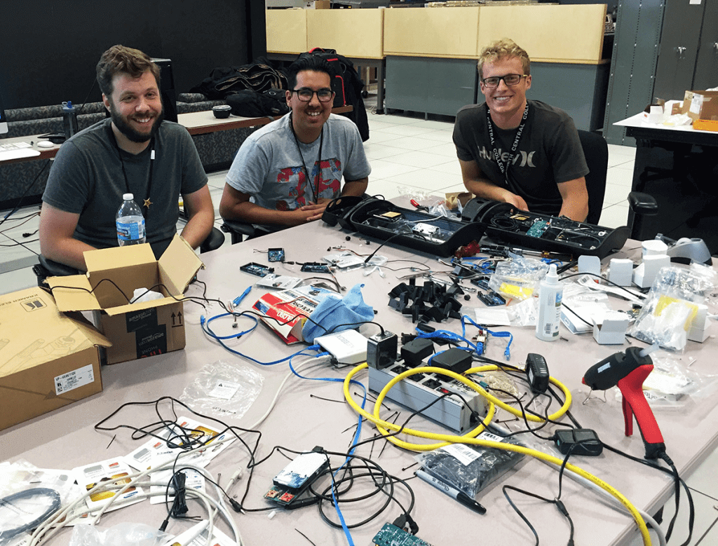 (Left to right) NIU students Adam Young and Adolfo Rodriguez, along with Joe Sortino of North Central College, assemble AoT nodes for the University of Chicago test bed.