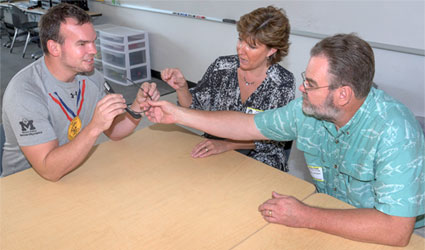 "Ackerman and NIU College of Education professors Toni Van Laarhoven and Jesse ""Woody"" Johnson examine a Google Glass."
