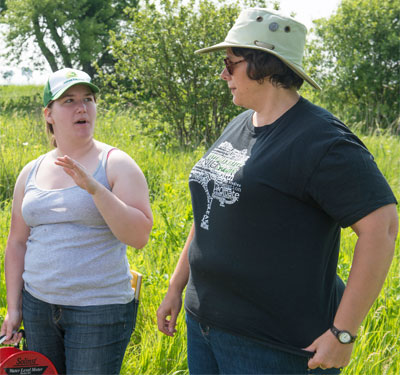 Melissa Lenczewski (right) and an NIU student work in the field with a water level meter.