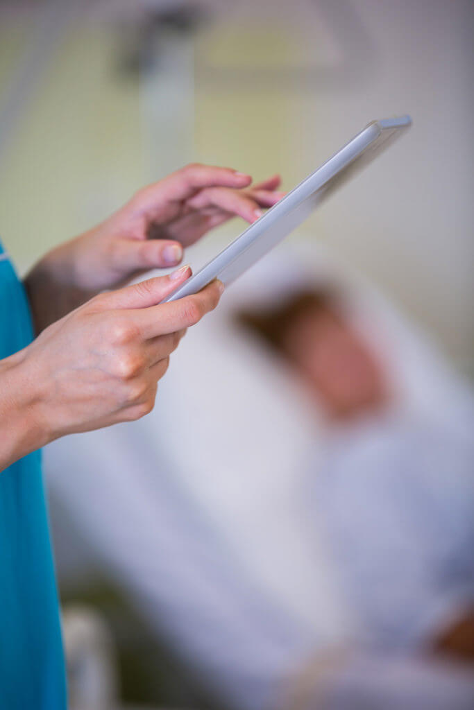 Nurse using digital tablet in hospital ward
