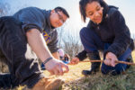 NIU Physical Education major Brandon Palmer helps fifth-grader Yvonne Chanda learn how to start a fire.