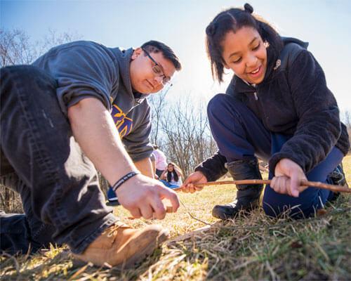 NIU Physical Education major Brandon Palmer helps fifth-grader Yvonne Chanda learn how to start a fire.