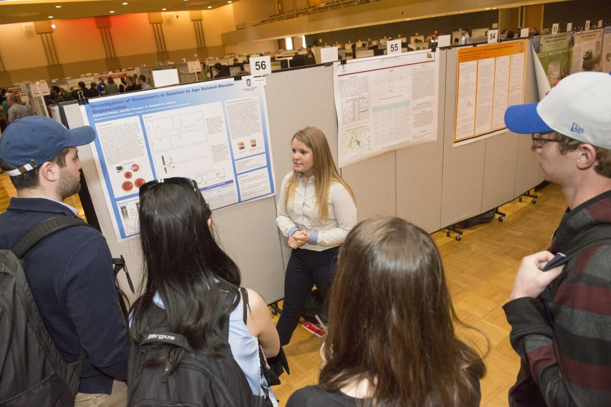 Freshman Katie Denius explains her research on macular degeneration to interested students