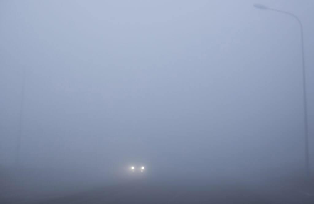 car on road.  heavy fog and haze