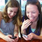 Teens texting and giggling