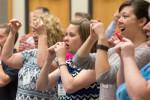 IL-CMP workshop participants practice singing vowel sounds with corresponding motions.