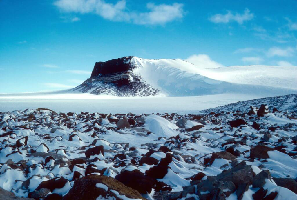 Sirius Group exposures near Mt. Fleming, Antarctica, circa 1986. The pattern of snow behind rocks shows the prevailing winds across the East Antarctic Ice Sheet. (Credit: Reed Scherer, Northern Illinois University.)