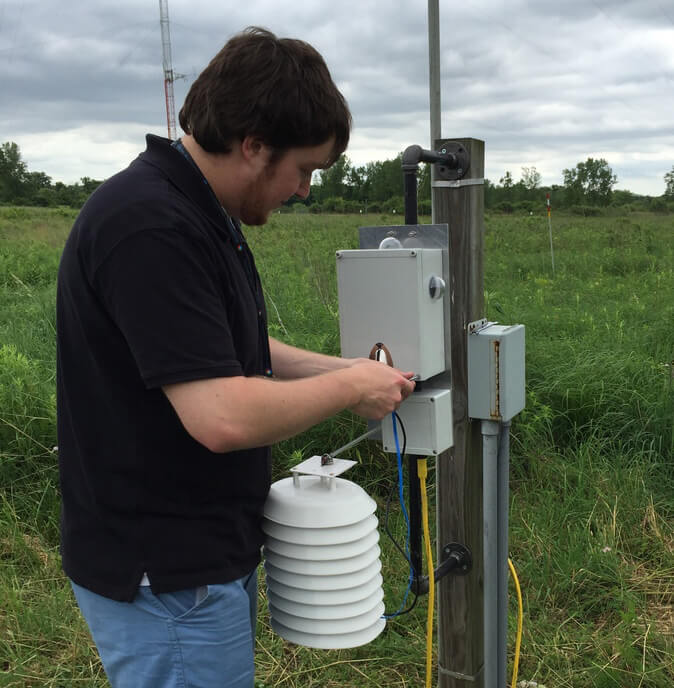 "Alex Wills sets up an ""ugly box"" equipped with sensors for the Array of Things project while interning at Argonne National Laboratory this past summer."