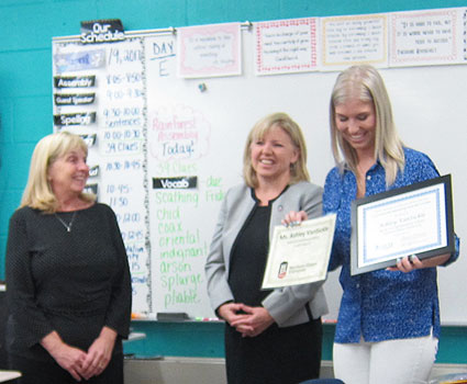 Ashley Van Sickle (right) receives her Outstanding Beginning Teacher Award from (left) Portia Downey, professional development coordinator in the NIU College of Education, and (center) Jennifer Johnson, the college's director of teacher preparation and development.